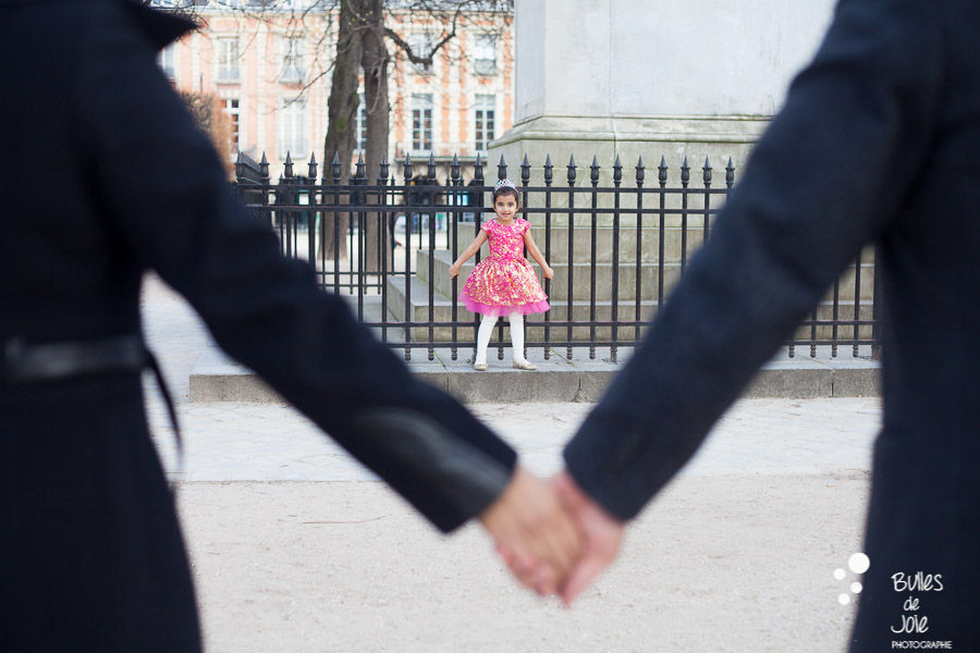 Parents holding their hands with their daughter in the backgroup, ready to run to them. Paris family photo session. More photos