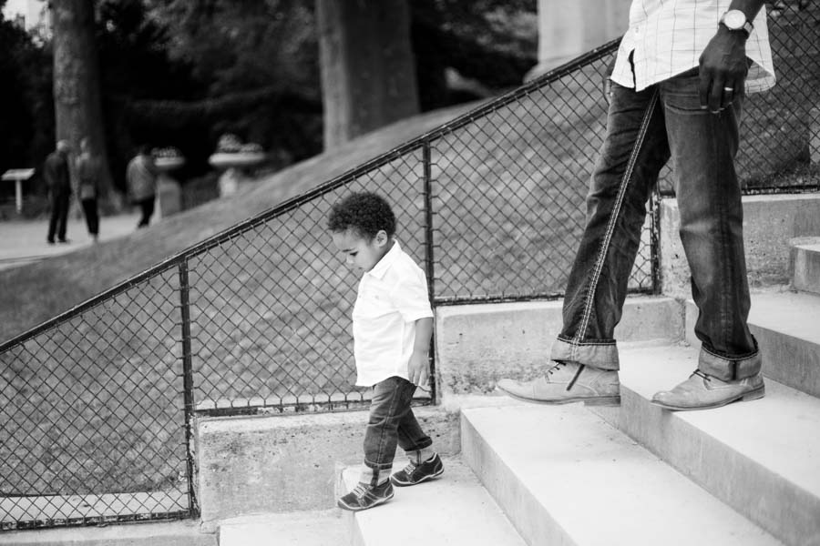 Black and white photo of a boy walking. Captured by Bulles de Joie, Paris family photographer.