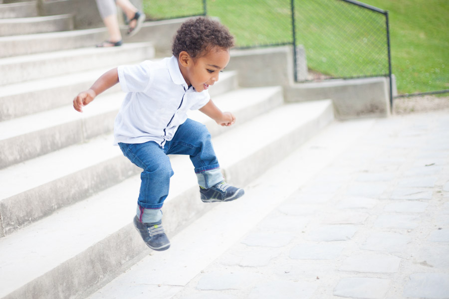 Little boy jumping during a family photo session in Paris. Captured by Bulles de Joie, Paris family photographer.