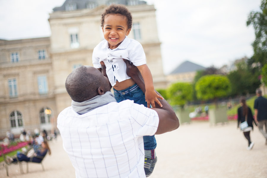 Dad holding his son in Luxembourg Garden in Paris. Captured by Bulles de Joie, Paris family photographer.
