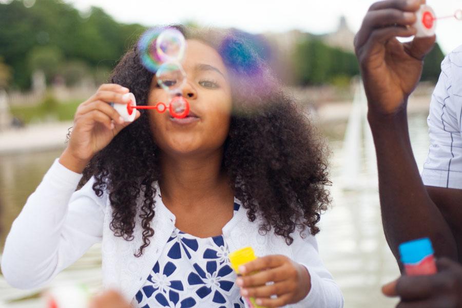 Petite fille s'amusant avec des bulles lors d'une séance photos. Souvenir immortalisé par Bulles de Joie, photographe famille à Paris et région parisienne, Hauts-de-Seine, Yvelines.