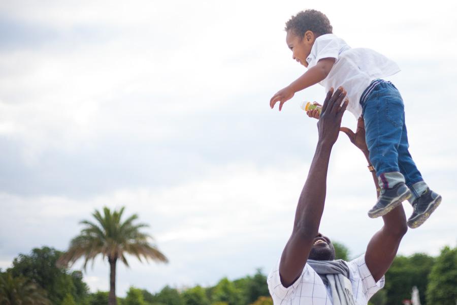 Un papa lancant son fils dans les airs, qui rit. Souvenir immortalisé par Bulles de Joie, photographe famille à Paris et région parisienne, Hauts-de-Seine, Yvelines.