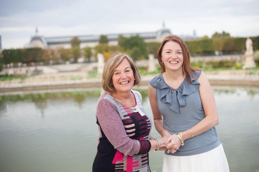 Une femme et sa maman se tenant les mains, souriant vers l'appareil photo. Souvenir immortalisé par Bulles de Joie, photographe famille à Paris et région parisienne, Hauts-de-Seine, Yvelines.