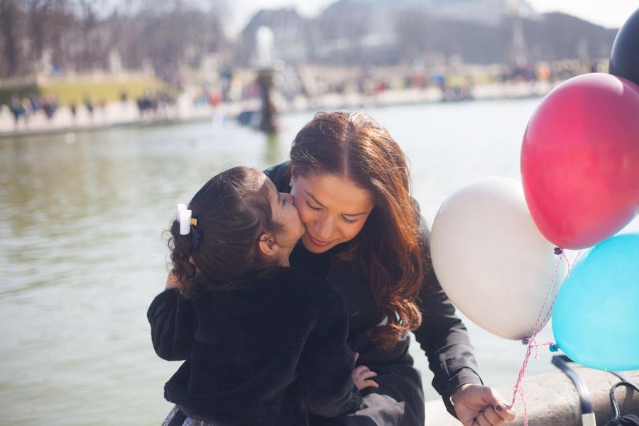 Une petite fille faisant une bisous sur la joue de sa mère, tenant des ballons. Souvenir immortalisé par Bulles de Joie, photographe famille à Paris et région parisienne, Hauts-de-Seine, Yvelines.