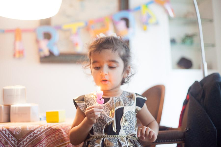 Petite fille soufflant une bougie pour ses 3 ans. Séance photos pour un anniversaire. Souvenir immortalisé par Bulles de Joie, photographe famille à Paris et région parisienne, Hauts-de-Seine, Yvelines.