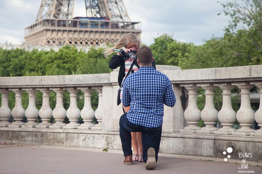 Man kneeling to ask her girldfriend to marry him and she's crying - surprise proposal captured by Bulles de Joie, photographer in Paris
