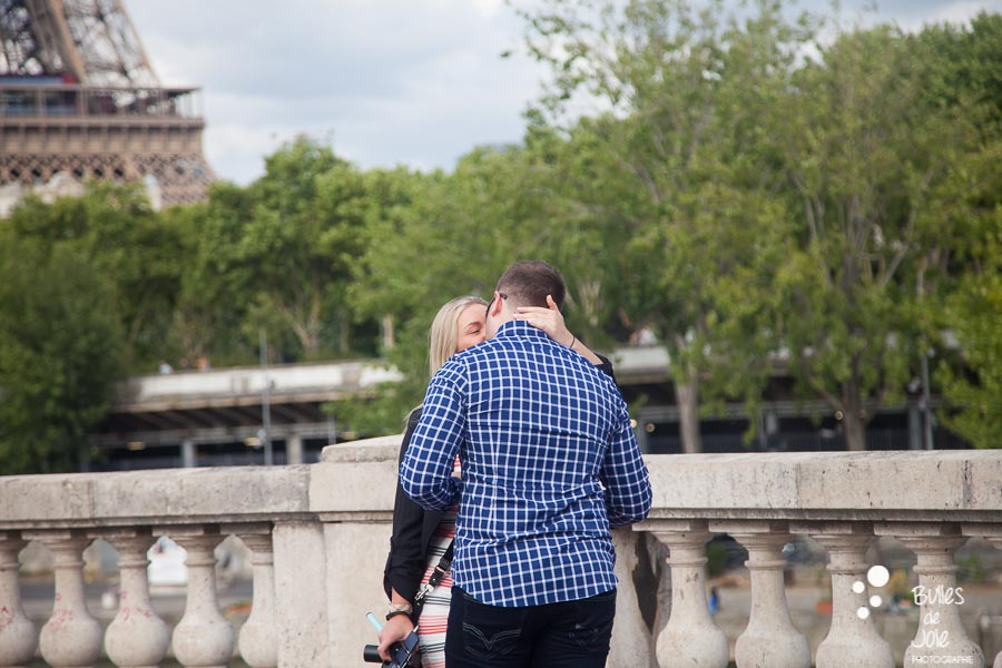 Woman kissing her boyfriend after his surprise proposal in front of the Eiffel Tower in Paris