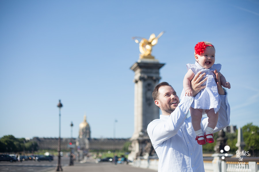 A dad lifting her daughter her. Family photoshoot in Alexander 3 Bridge in Paris. More photos: