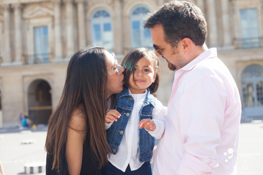 Parents kissing their daughter on a family photo session in Paris, close to the Louvre. More photos: https://www.bullesdejoie.net/en/2017/09/14/eifel-tower-family-photoshoot-family-s/