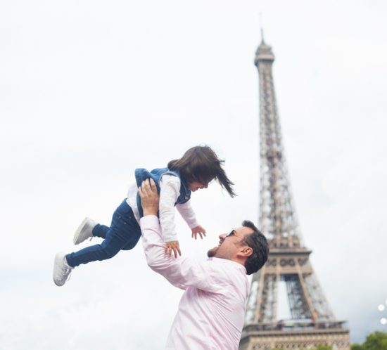 Eifel Tower family photoshoot. A dad making her little girld fly into the air. More photos from Bulles de Joie, paris photographer: