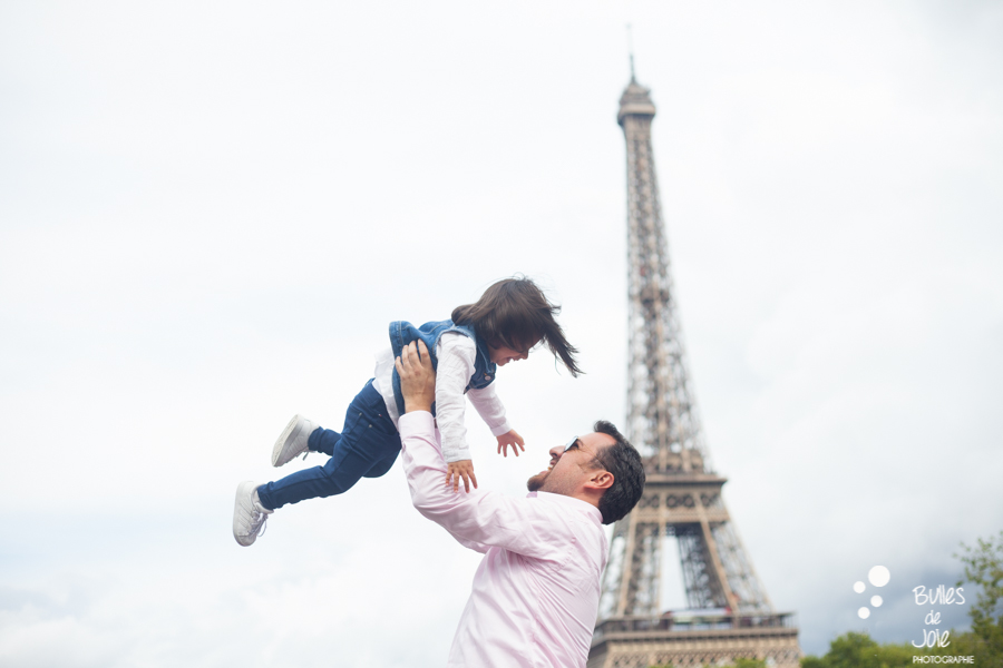 Eiffel Tower family photoshoot. A dad making her little girld fly into the air. 3 tips to feel comfortable in front of the camera.