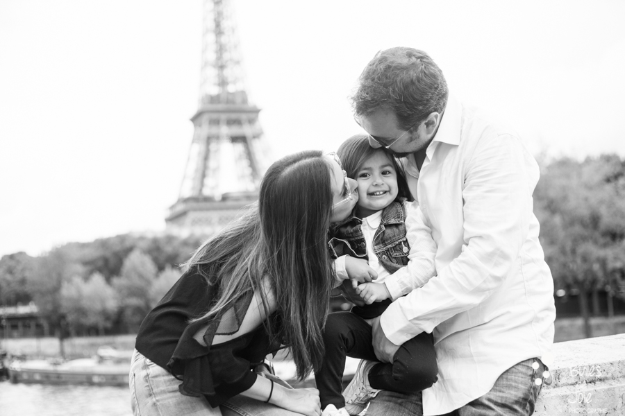 Black and white photo of parents kissing their little girl during a photoshoot in Paris in front of the Eifel Tower. More photos: https://www.bullesdejoie.net/en/2017/09/14/eifel-tower-family-photoshoot-family-s/