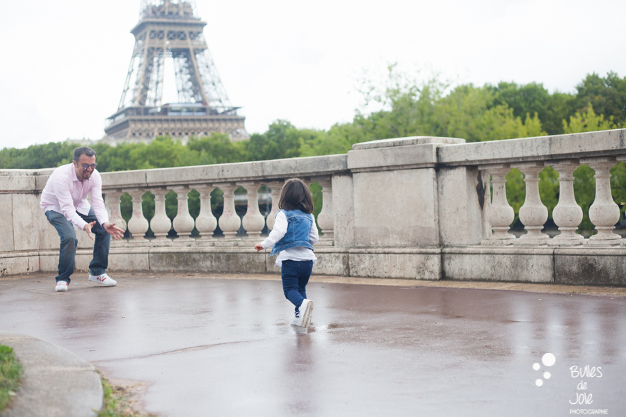 Little girl running in her dad's hands. Eifel Tower family photoshoot with the Paris photographer Bulles de Joie. More photos: https://www.bullesdejoie.net/en/2017/09/14/eifel-tower-family-photoshoot-family-s/