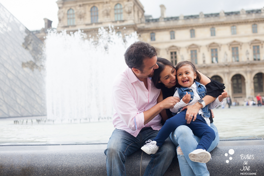 Parents tickling her daughter. Family photoshoot at the Louvre. More photos: https://www.bullesdejoie.net/en/2017/09/14/eifel-tower-family-photoshoot-family-s/