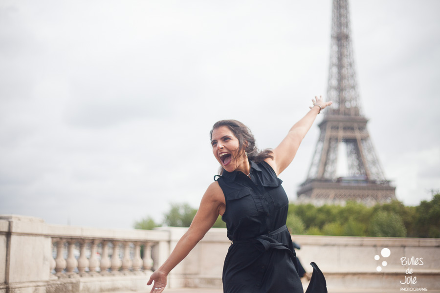 Woman enjoying life in front of the Eiffel Tower. Wedding anniversary gift for her in Paris. More photos: