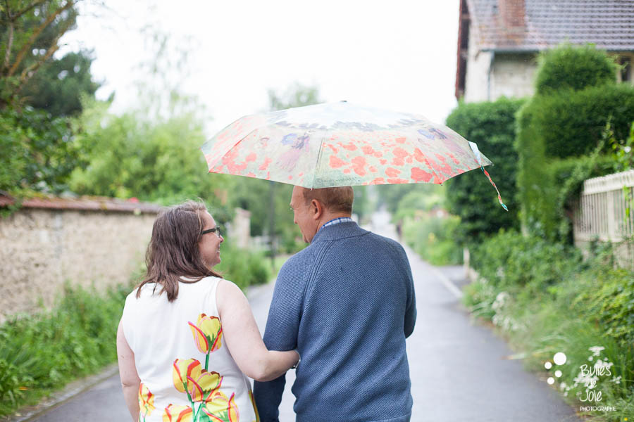 Proposal & engagement photo session in Giverny, couple walking down the street under an umbrella