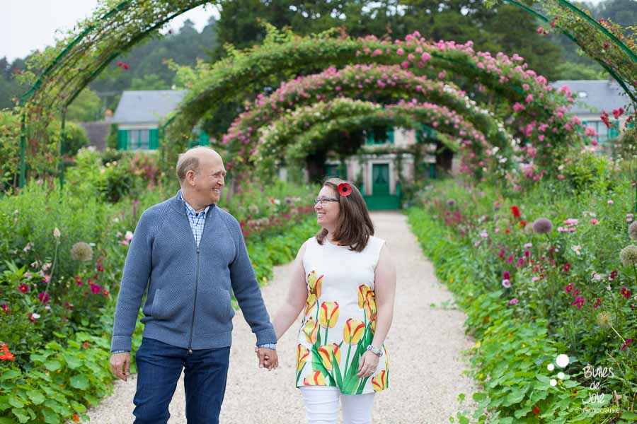 Proposal & engagement photo session in Giverny, lovers walking down a flowered alley