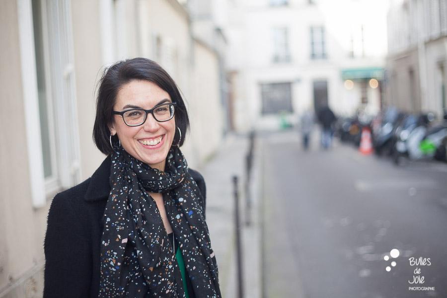 Portrait d'une femme entrepreneure souriante dans les rues de Paris. Par Bulles de Joie, photographe de femmes entrepreneures