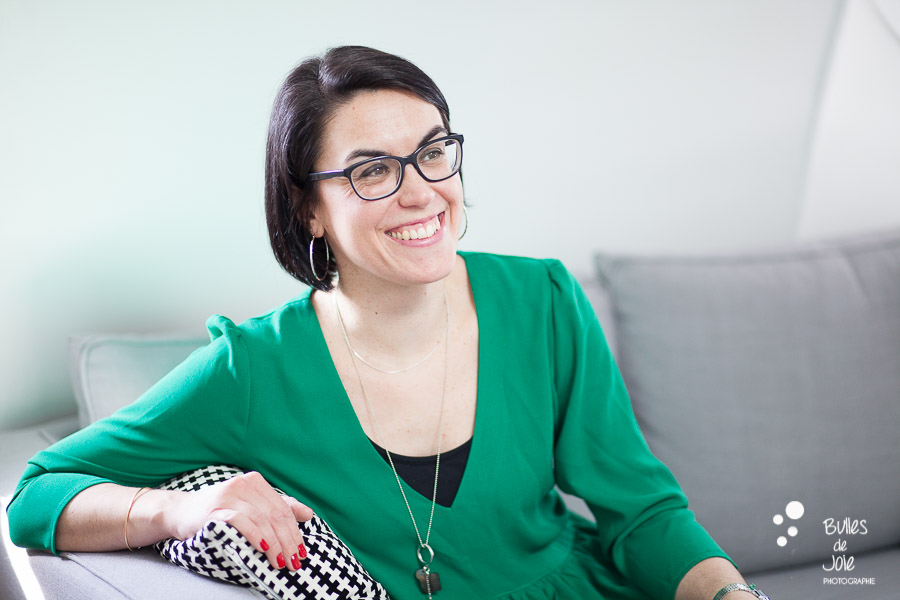 Portrait naturel d'une femme entrepreneure souriante dans un lieu cosy. Par Bulles de Joie, photographe de femmes entrepreneures