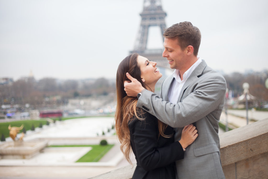 Romantic engagement picture of a couple in front of the Eiffel Tower by Bulles de Joie, Engagement Photographer in Paris