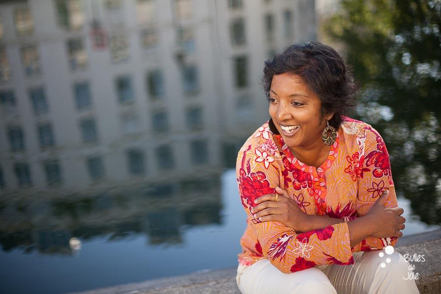 Portrait naturel d'une femme entrepreneure souriante au Canal St Martin, Paris. Par Bulles de Joie, photographe de femmes entrepreneures