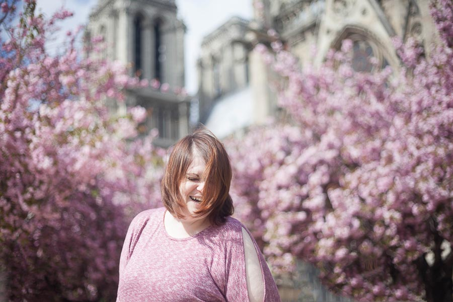 Woman laughing with cherry blossoms in the background | Paris portrait photoshoot