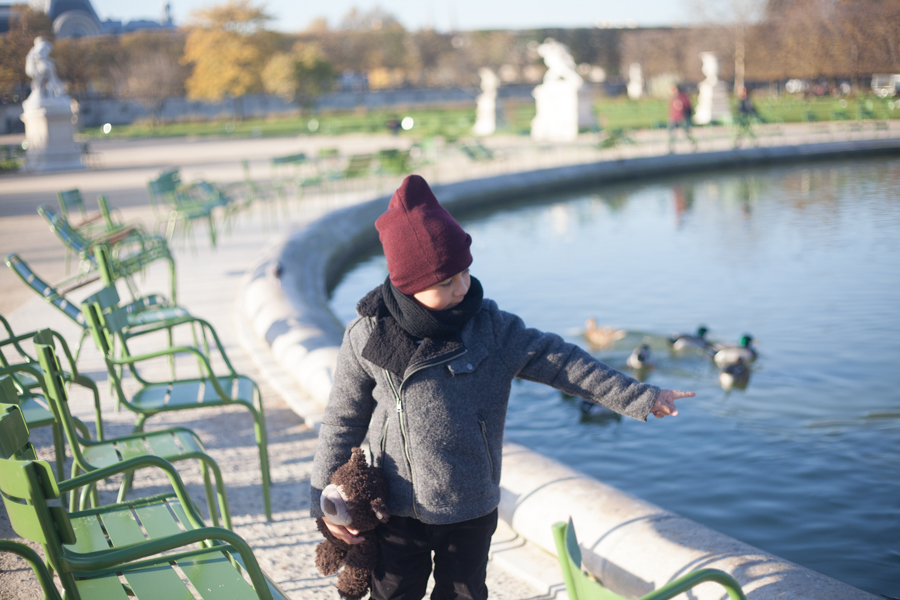 Kid showing ducks to his mum on a family photoshoot in Paris