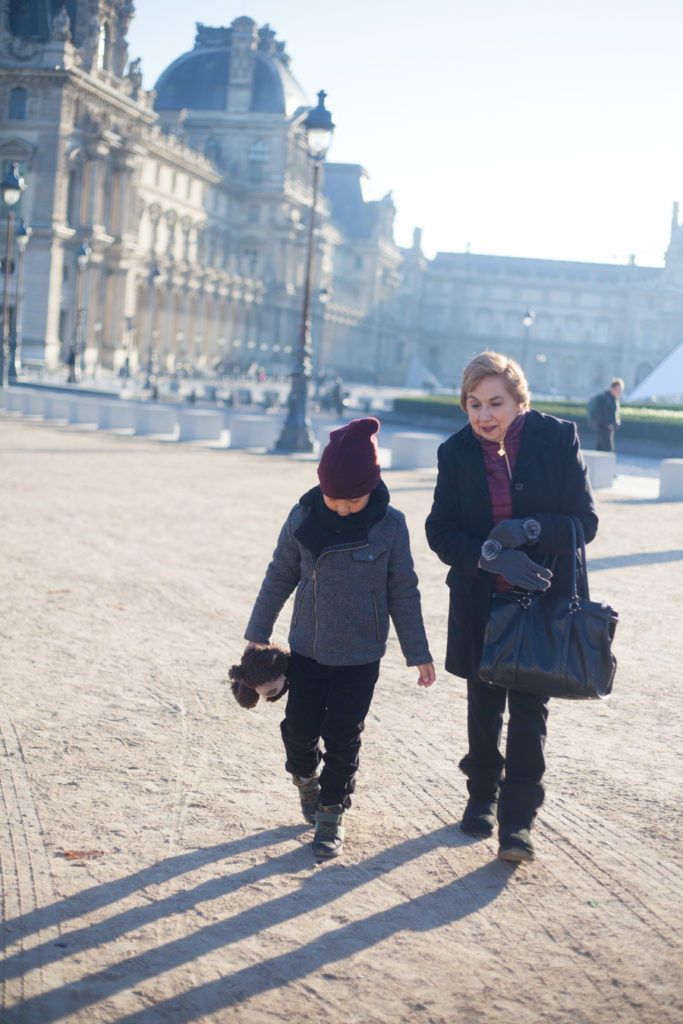 Boy and his grandma walking from the Louvre Pyramid to Tuileries Garden
