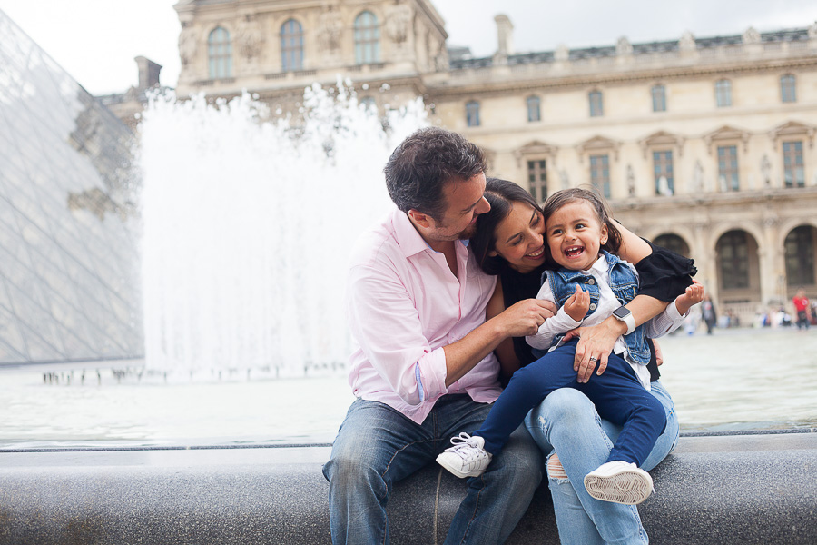 Family shot at the Louvre Pyramid, by Bulles de Joie, Paris family Photographer