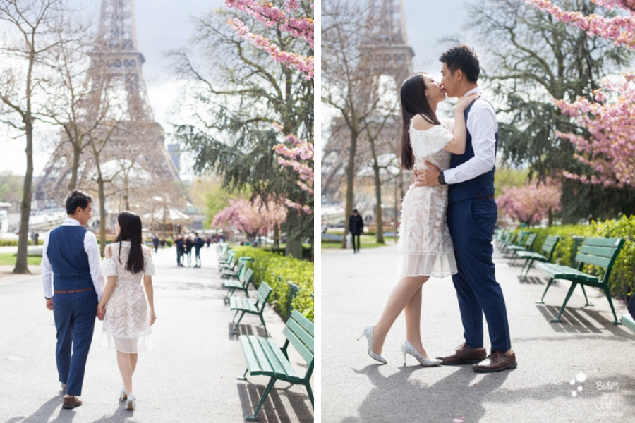 Spring pre-wedding photoshoot Paris - Couple walking and kissing in front of the Eiffel Tower and pink cherry blossoms