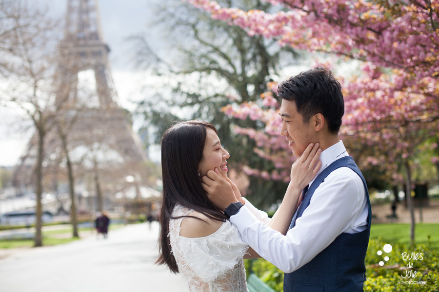 Spring pre-wedding photoshoot Paris, cute couple in front of the Eiffel Tower and surrounded by pink cherry blossoms