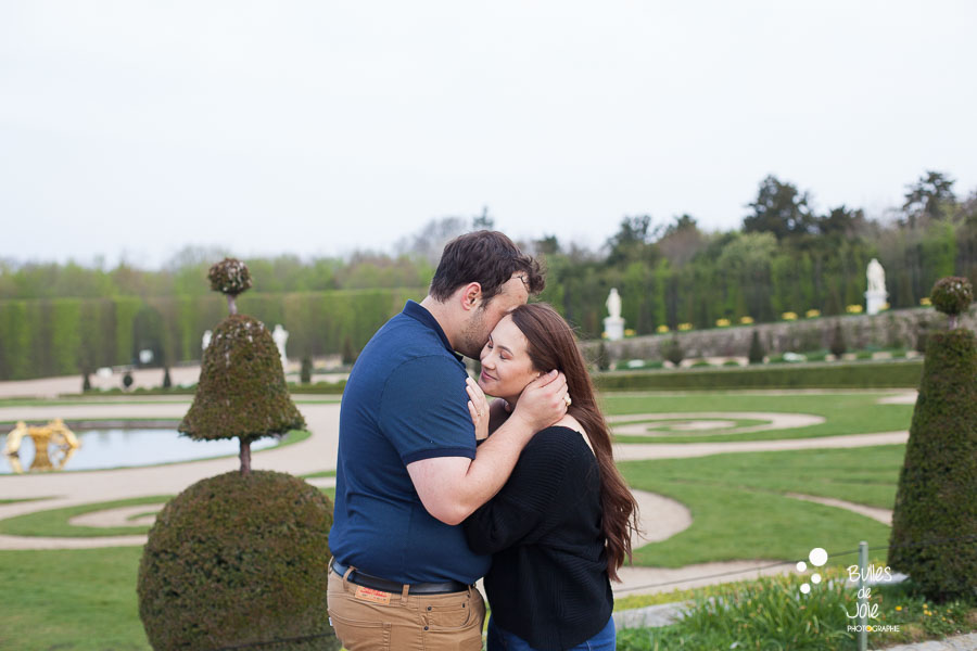 Man whispering a secret to his future wife. Couple photoshoot Versailles Gardens