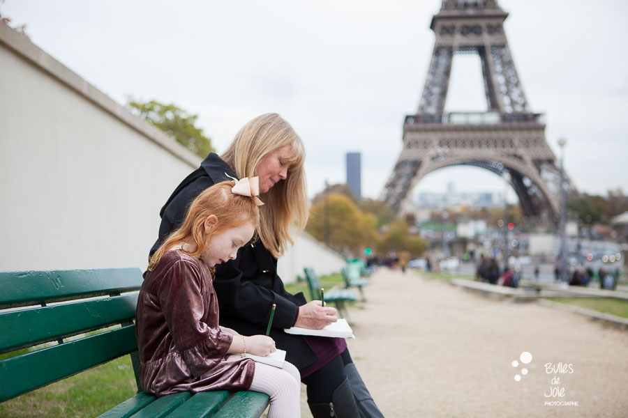Girl and grandma drawing the Eiffel Tower. Captured by Bulles de Joie, Paris family photographer.