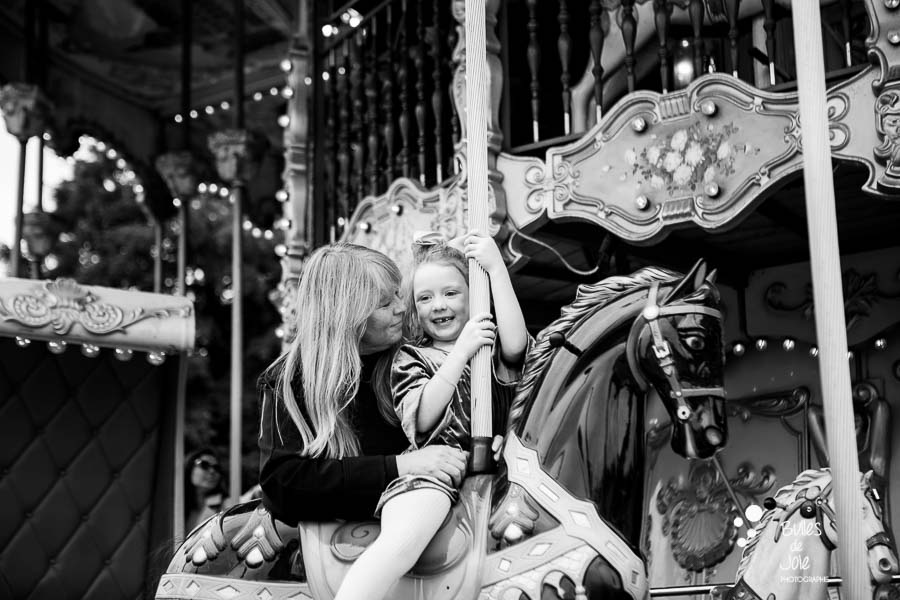 Photo of a girl and her grandma on a carroussel in Paris with the Eiffel Tower in the background.