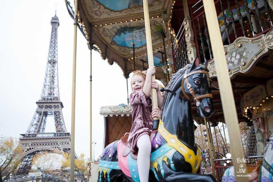 Photo of a girl on a carroussel in Paris with the Eiffel Tower in the background