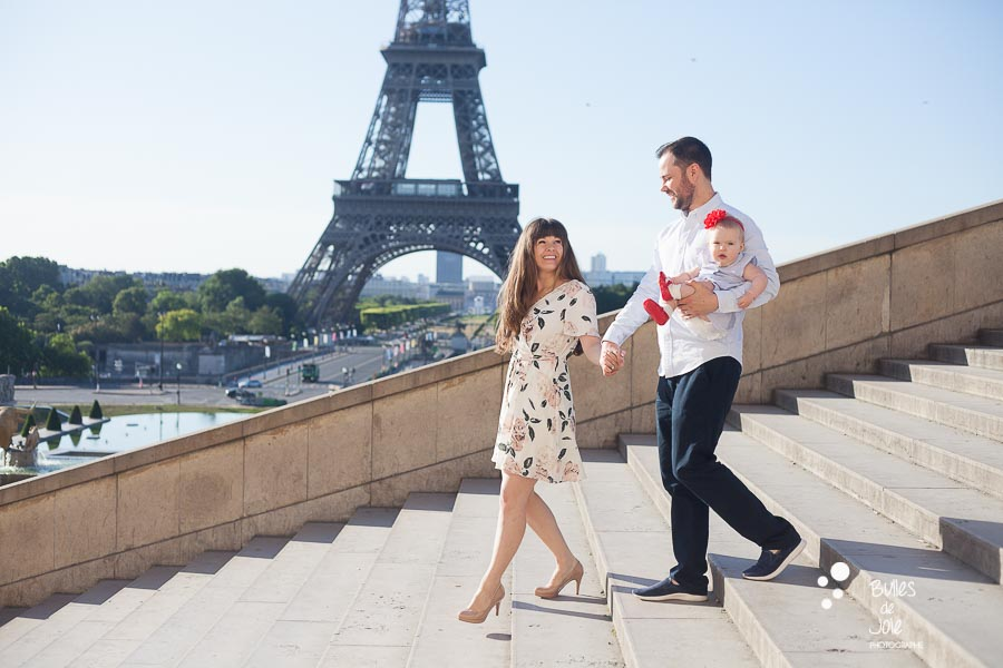 Couple with their child walking down the stairs at Trocadero with the Eiffel Towr behind them.