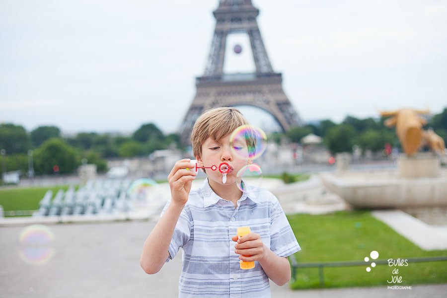 Young boy blowing bubbles at Trocadero gardens, Eiffel Tower.