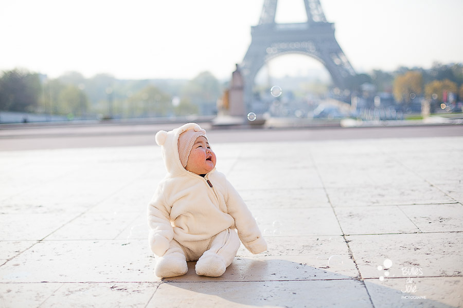 Cute little toddler sitting in front of the Eiffel Tower, Paris.