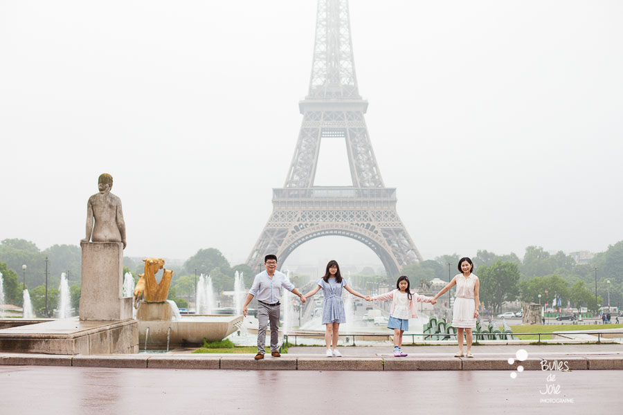 Family of 4 holding their hands in front of the Eiffel Tower. Family photoshoot by Bulles de Joie.