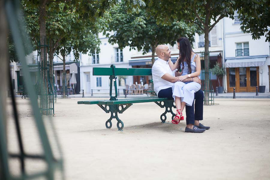 Paris photoshoot - couple sitting on a bench at Place Dauphine in Paris