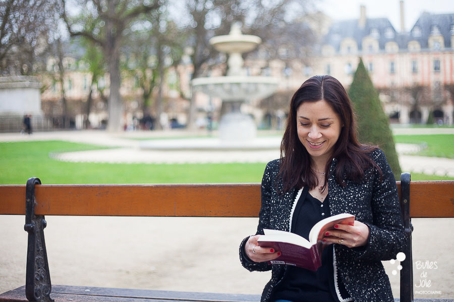Paris photoshoot Marais - solo traveler reading her book in place des Vosges