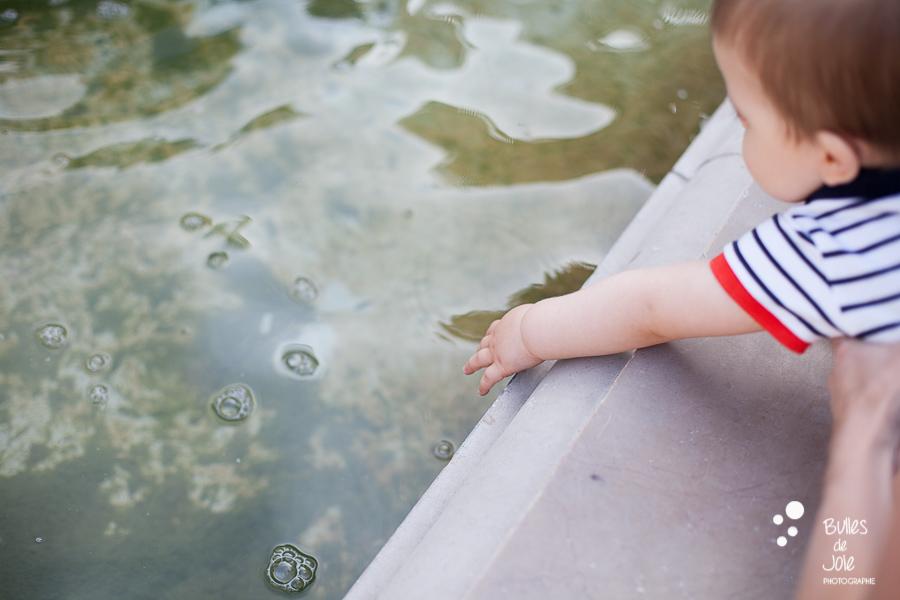 Bébé touchant l'eau des mains au jardin du Palais Royal, Paris