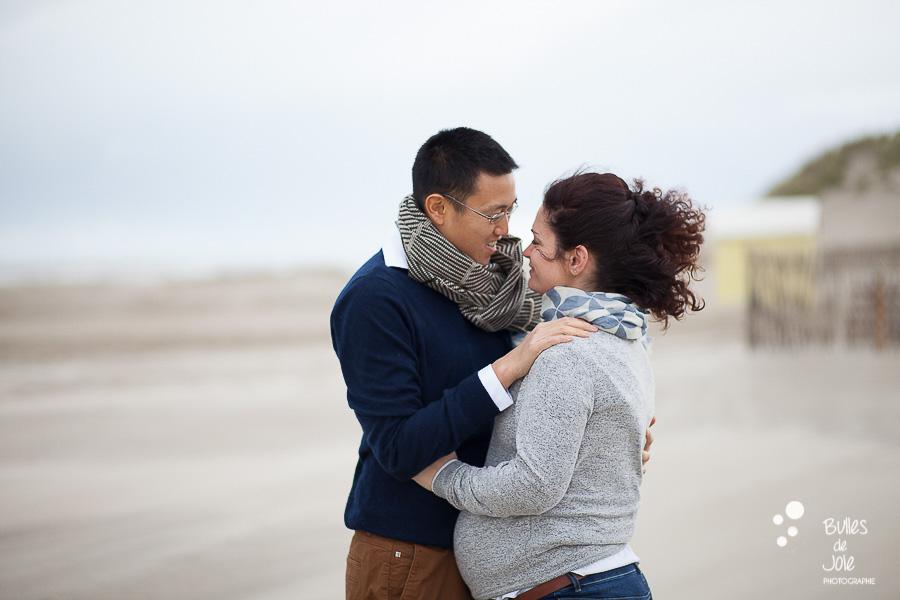 Couple complice se regardant dans les yeux lors d'une séance photos en bord de mer