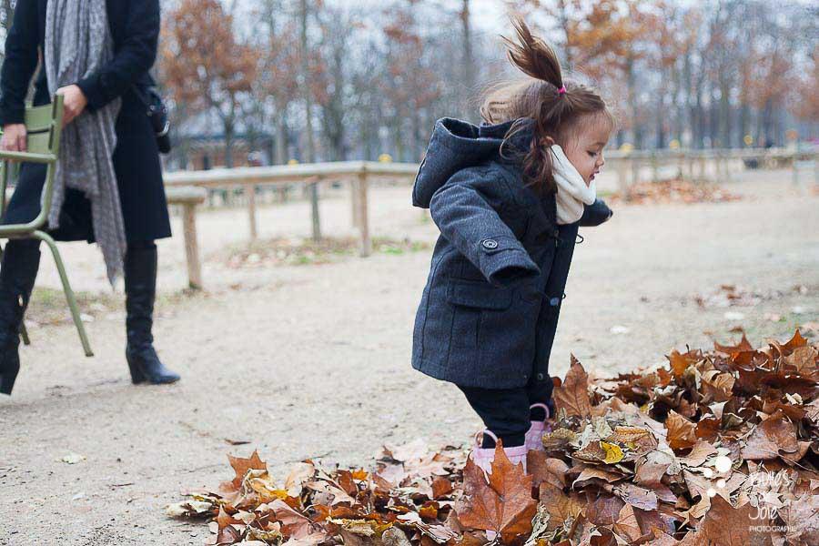 Petite fille sautant dans les feuilles mortes - séance photos famille en Automne