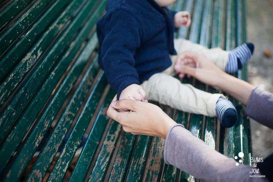 Maman tenant la main de son bébé, assis sur un banc